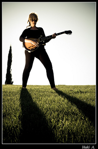 Woman playing a guitar on grass
